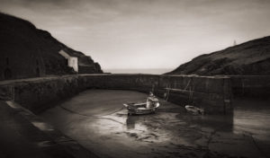 Porthgain, Pembrokeshire, Wales. This tiny little port used to be at the forefront of the area's Slate and hardcore industry. The logistical infrastucture that delivered the materiels to the port for shipping all over the world can still be seen on the hill to the left, and are an impressive sight.